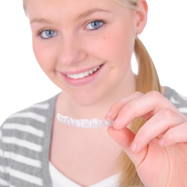 A blonde teenager holding Invisalign clear aligners