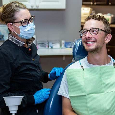 A young man sitting in a dental chair next to one of our dental assistants