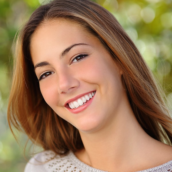 A young woman with long brown hair and a beautiful smile