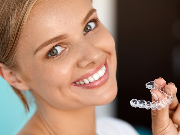 A blonde woman holding Invisalign clear aligners