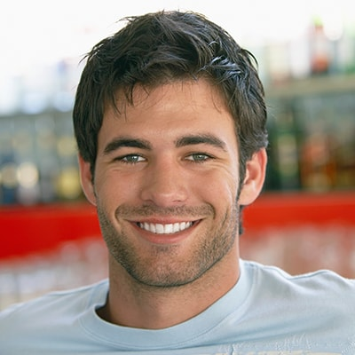 A young man with a beard smiling