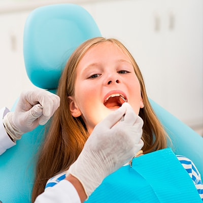 Our dentist placing a dental sealant in a little girl's mouth