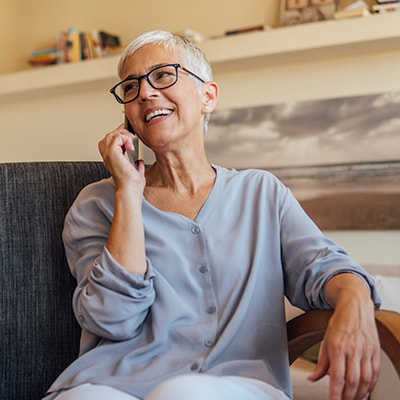 An older woman talking on the phone from her sofa