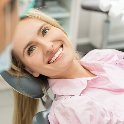 A blonde woman lying in a dental chair