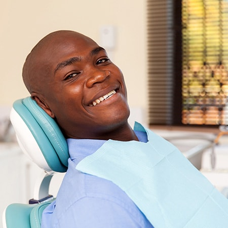 A man wearing a bib sitting in a dental chair