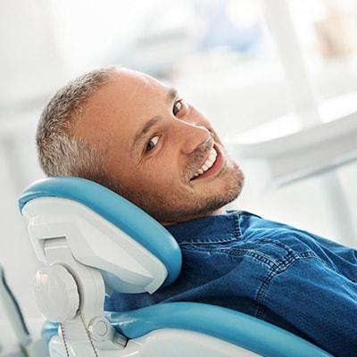A man with a beard reclining in a dental chair